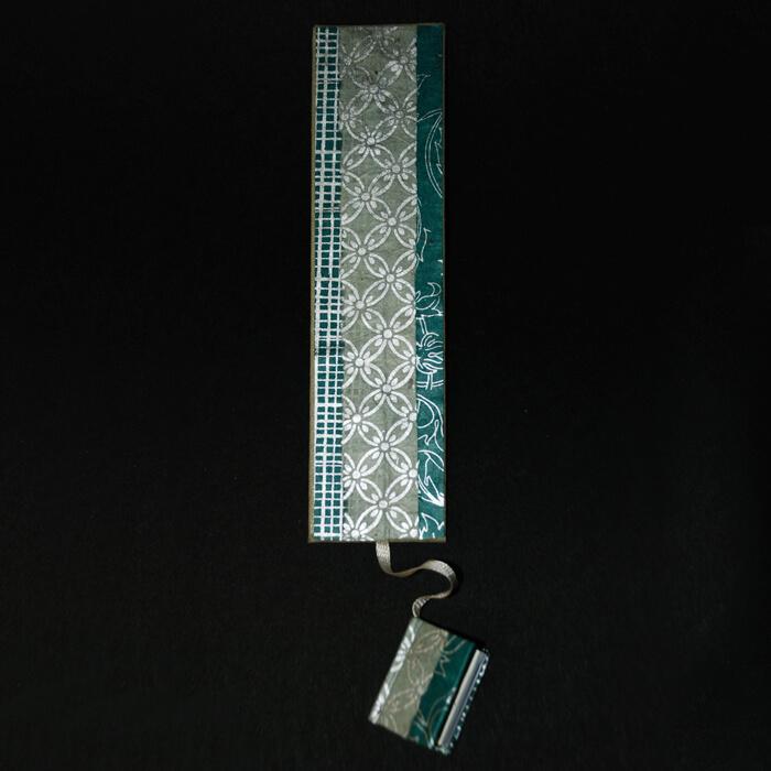 Lesezeichen mit türkis-silbernem Muster und kleinem Buch
