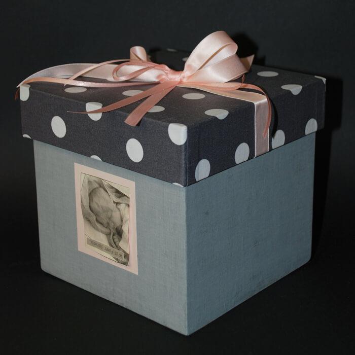 Geschenkbox blau mit rosa Schleife und Babyfoto