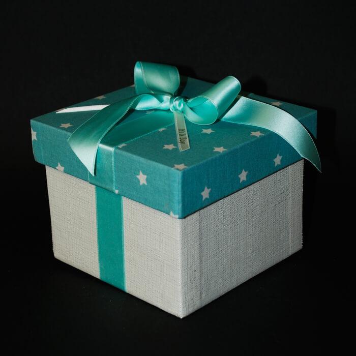 Geschenkbox in hellblau mit Sternenmuster und Schleife