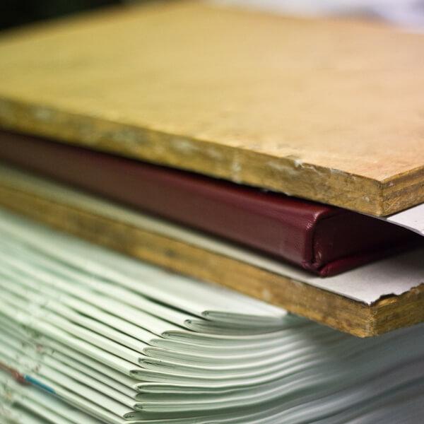 Buch mit rotem Einband zwischen zwei Holzplatten